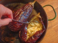 spooning out the creamy aubergine flesh