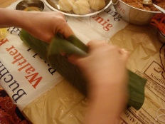 wrapping the banana leaves around the dough and stew